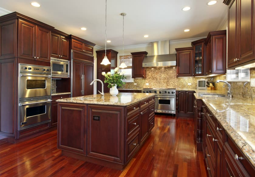 Brown kitchen setup with beautiful hardwood flooring and has a large center island with a granite countertop matching the countertops of the kitchen counters.