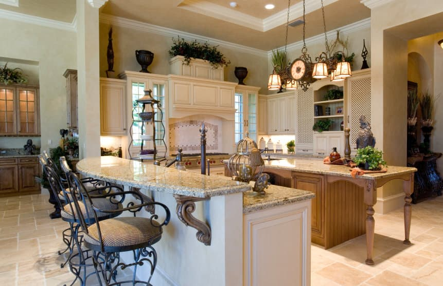 Mediterranean-style kitchen featuring a breakfast bar island along with a separate center island, both featuring granite countertops. The center island is lighted by gorgeous ceiling light hanging from the tray ceiling.