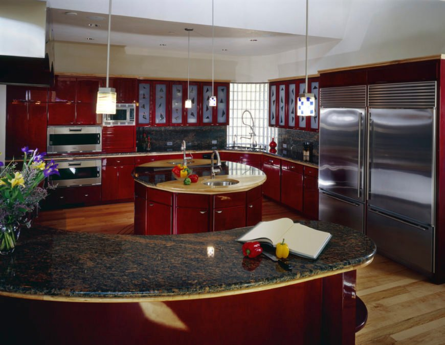 A red and spacious kitchen featuring a round center island and an L-shaped kitchen counter, along with a curved bar counter both with stunning granite countertops.
