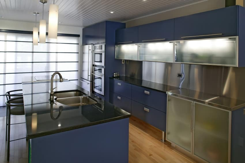 A navy blue-themed kitchen with a black kitchen counter and has a center island with a black countertop, and has space for a breakfast bar lighted by pendant lights.