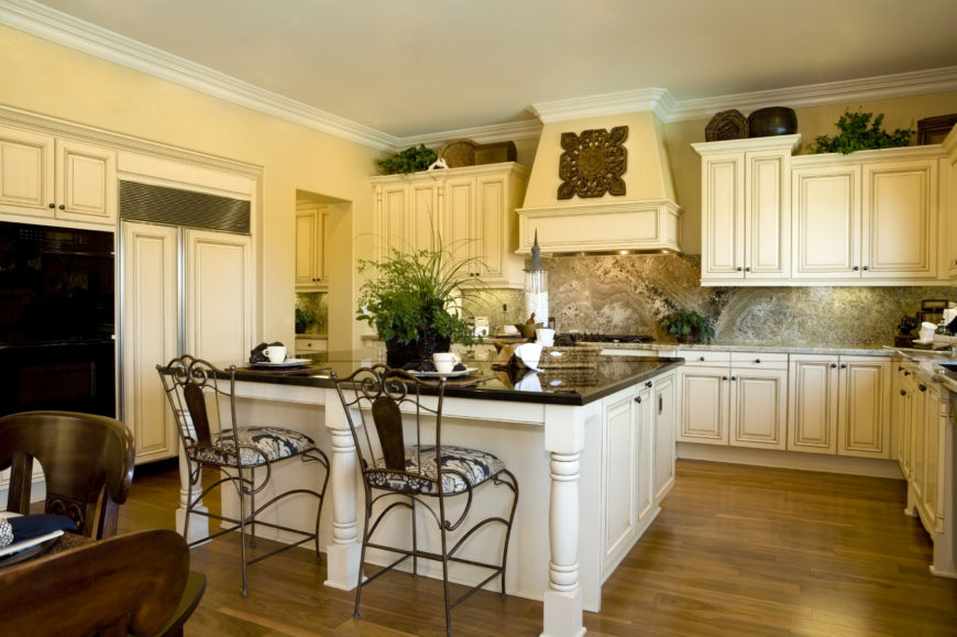 A spacious L-shaped kitchen with white cabinetry and kitchen counters, along with a large center island with a black countertop and has space for a breakfast bar.