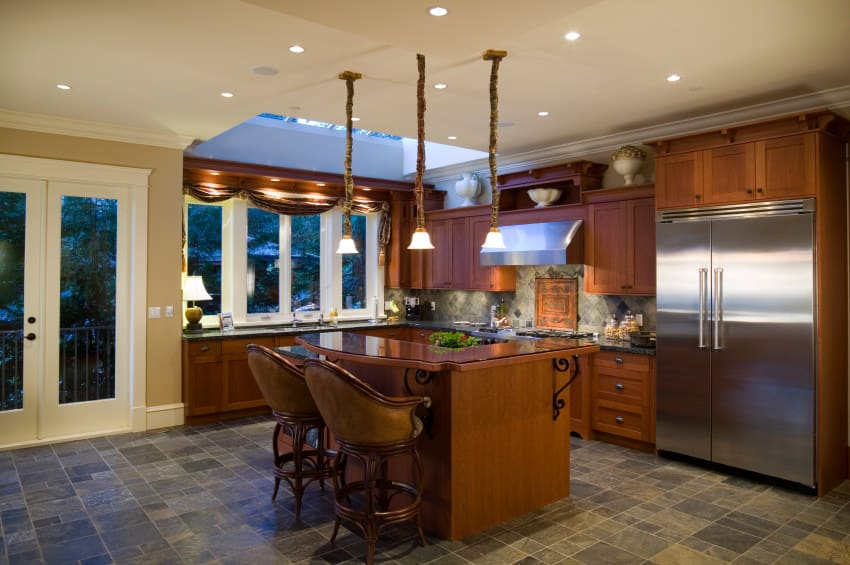 A focused shot at this kitchen's L-shaped style and the brown breakfast bar island boasting elegant chairs and is lighted by pendant lights.