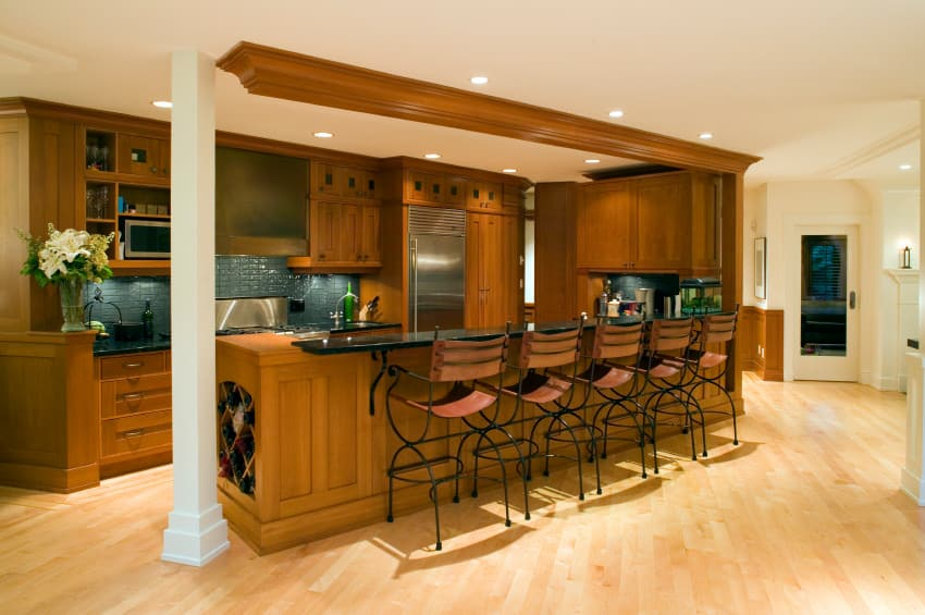 Brown kitchen with a black breakfast bar counter paired with stylish seats. The island offers a small wine rack on the its side. The kitchen is lighted by recessed lights.