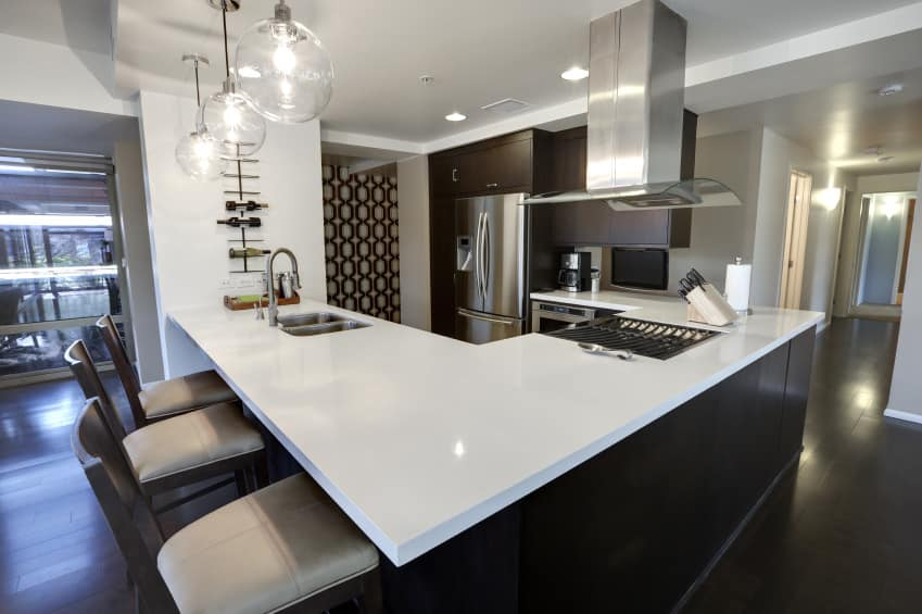 Modern kitchen featuring a white kitchen counter with a breakfast bar, lighted by pendant lights.