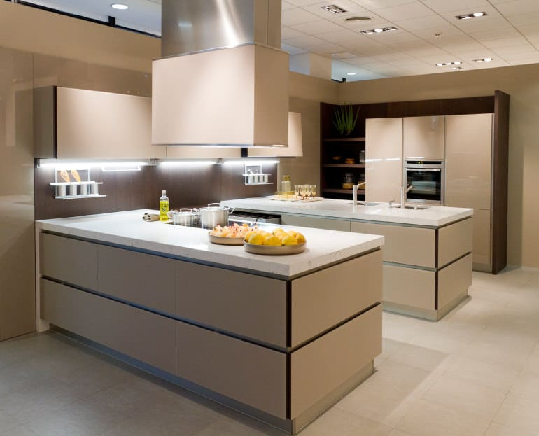 A focused look at this modern kitchen's two island counters with white marble countertops.