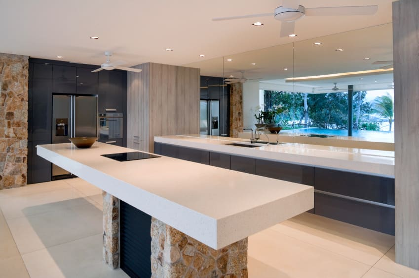 A focused shot at this contemporary kitchen's stunning center island with a white countertop matching the kitchen counter's countertop.