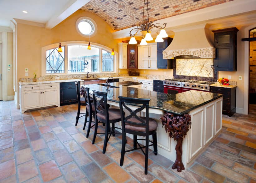 A spacious kitchen featuring terracotta tiles flooring and a stunning ceiling. The kitchen boasts a large U-shaped center island with a black marble countertop and has space for a breakfast bar.
