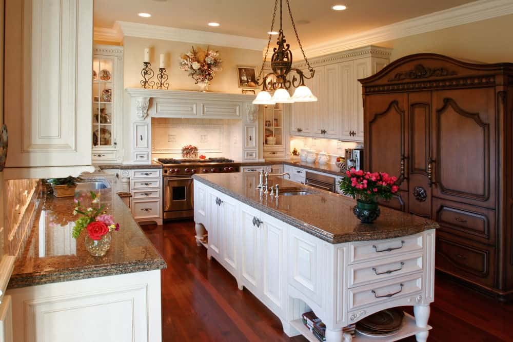 This kitchen has hardwood floors and light yellow walls. It has granite countertops and a long center island with built-in cabinetry, lighted by a gorgeous ceiling light.