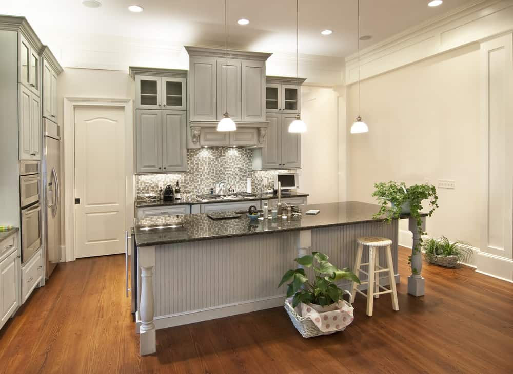 A medium-sized kitchen featuring hardwood flooring and gray cabinetry. It has a stylish black kitchen counter and has a center island with the same countertop.