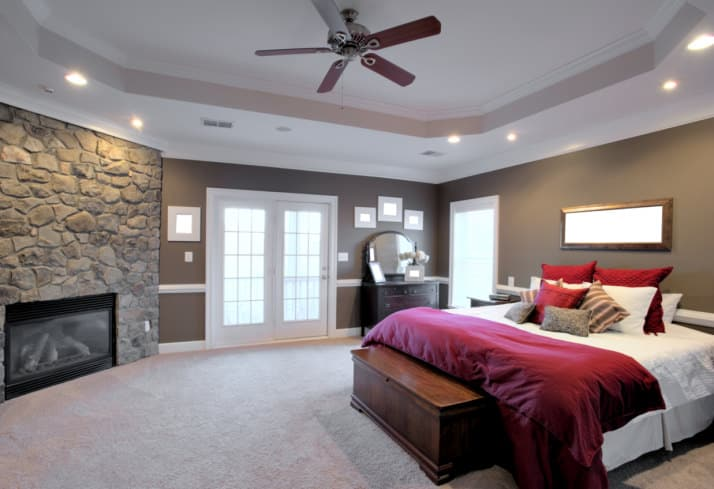 A spacious primary bedroom with gray walls and carpeted flooring, along with a tray ceiling. The room offers a large cozy bed along with a large stone corner fireplace.