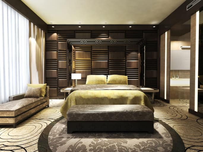 A primary bedroom boasting an elegant wall and attractive carpet flooring topped by a round classy rug matching the seats. The bedroom also offers its own bathroom on the side.