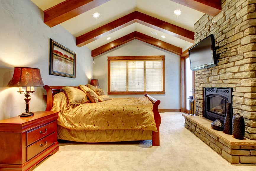 A spacious primary bedroom featuring carpeted flooring and a tall ceiling with large exposed beams. The room offers an elegant bed setup lighted by gorgeous table lamps on both sides. The room has a large brick fireplace in front, along with a TV on top.