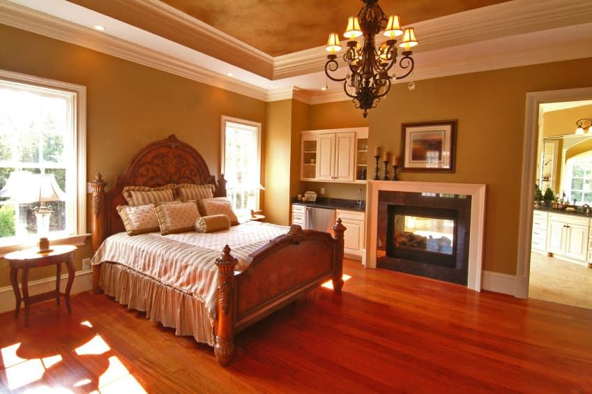 This primary suite offers a nice bed set and a fireplace on the side. The suite also has its own bathroom. The room is surrounded by brown walls and a tray ceiling.
