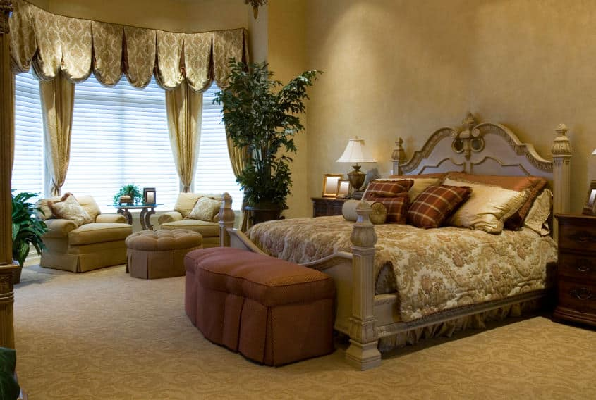 A spacious primary bedroom with an elegant bed setup. The room offers a sitting area by the windows. The room also has carpeted flooring and a tall ceiling.