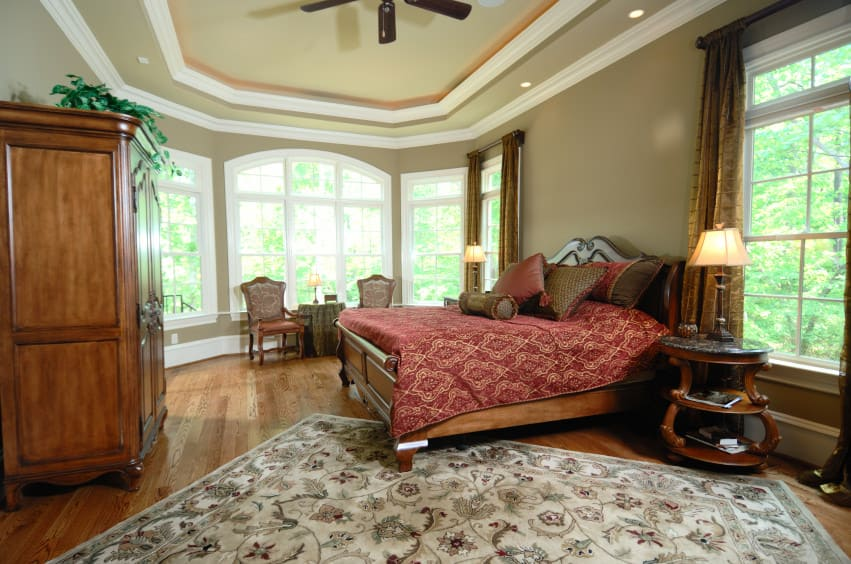 Spacious primary bedroom featuring hardwood flooring topped by an area rug along with a tray ceiling. The room offers a wooden cabinet along with a large bed.