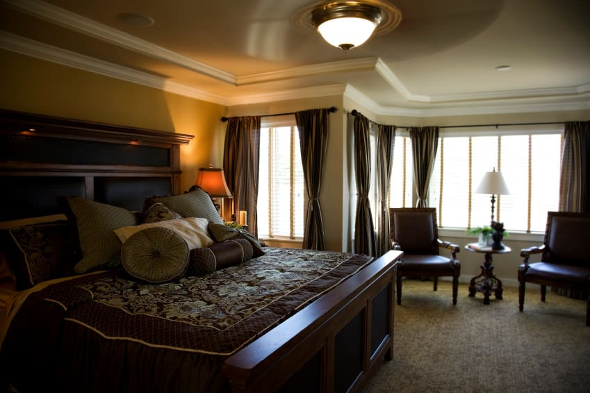 A spacious primary bedroom boasting a large luxurious bed setup along with a sitting area near the windows.