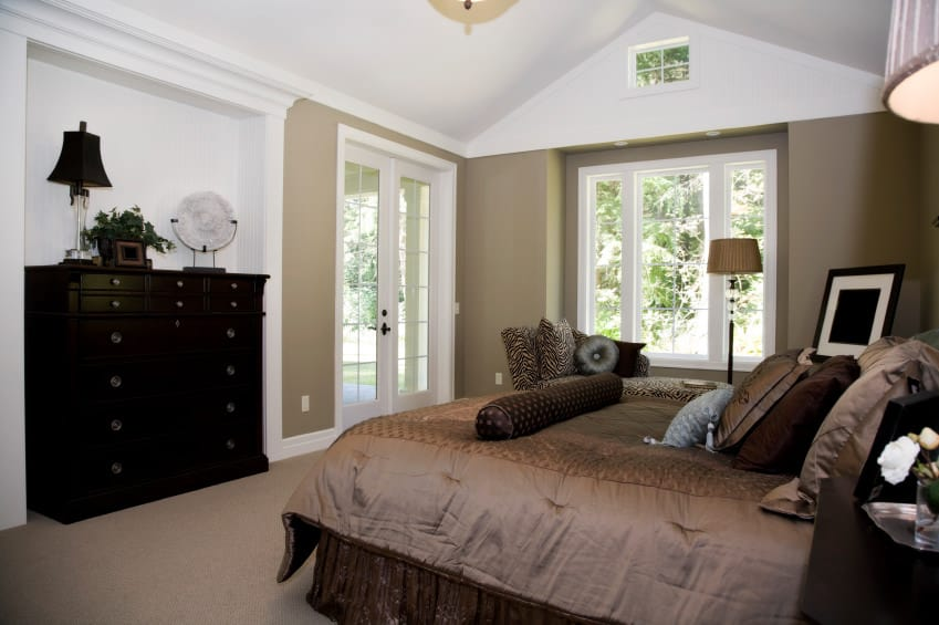 A primary bedroom with brown carpet flooring and brown walls. It offers a cozy brown bed and a doorway leading to the home's patio area.