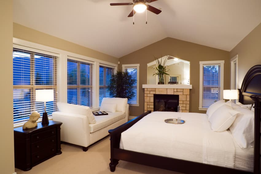 Medium-sized primary bedroom featuring a white couch and a stone fireplace, along with a nice bed set surrounded by brown walls.