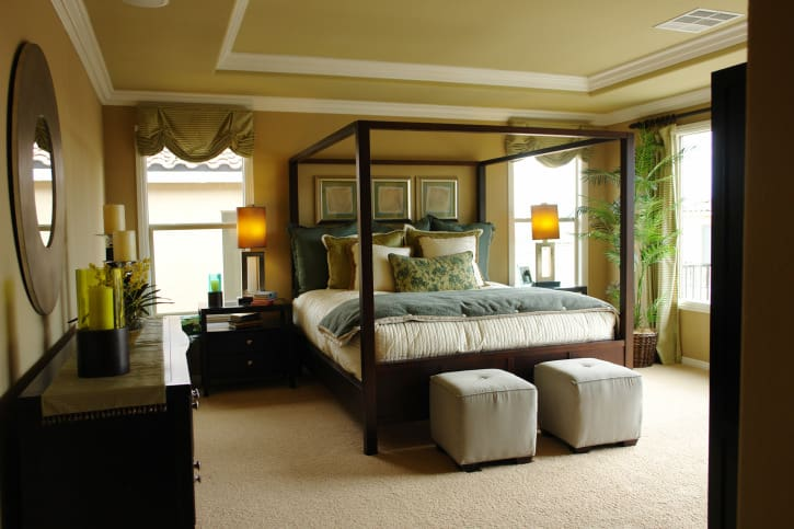 Country-style primary bedroom with yellow walls and a tray ceiling, along with carpeted flooring. The bed setup is lighted by table lamps on both sides.
