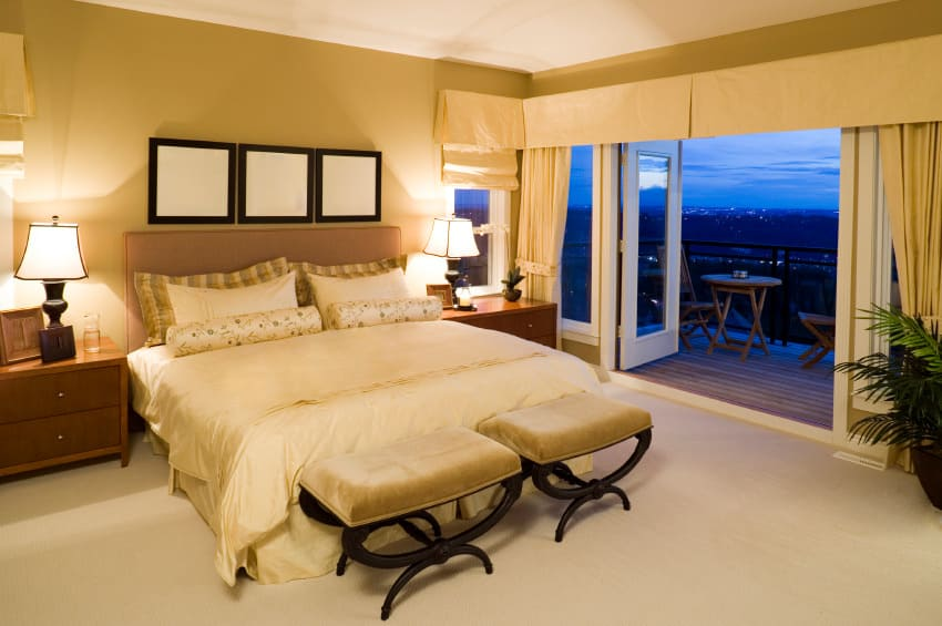 A primary bedroom boasting a nice bed set lighted by two table lamps. The room has a doorway leading to the home's private balcony area.