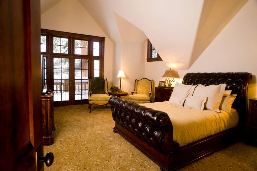 A medium-sized primary bedroom with a custom ceiling and gorgeous decorated carpet flooring. The room offers a luxurious bed, along with a sitting area on the side.