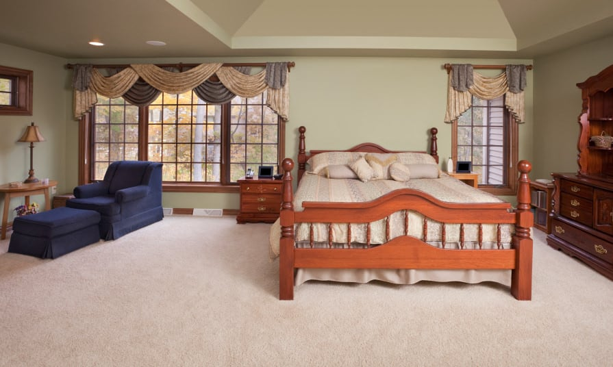 A spacious primary bedroom boasting a classy bed surrounded by olive green walls and has carpet flooring.