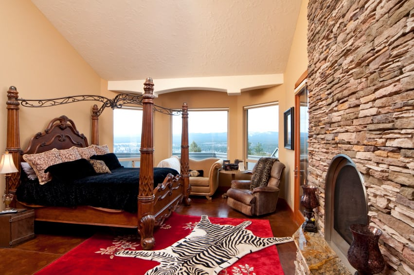A primary bedroom featuring an elegant bed setup with a cozy sitting area on its side. The room also offers a large stone fireplace.