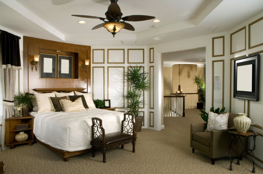 A primary bedroom featuring a gorgeous bed set lighted by two wall sconces. The room is surrounded by elegantly decorated walls.