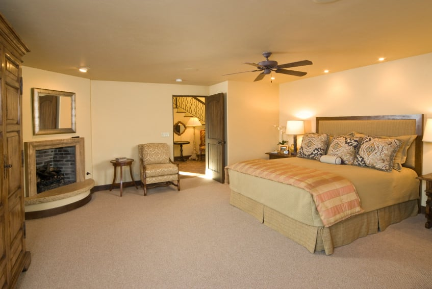 A spacious primary bedroom with carpeted flooring, and pieces of rustic furniture. The brown bed is lighted by table lamps on both sides.