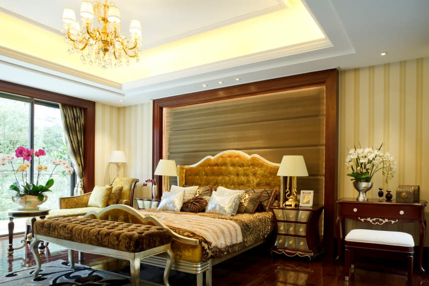 A primary bedroom boasting a luxurious bed setup along with elegant walls and a lovely tray ceiling with a gorgeous chandelier hanging from it.