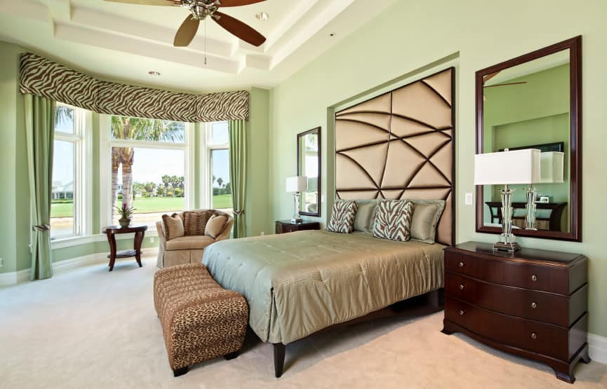 Primary bedroom boasting a luxurious bed set along with a gorgeous ceiling and surrounded by green walls and carpeted flooring.