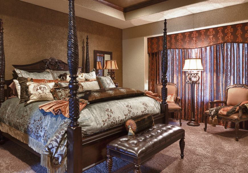 A focused look at this primary bedroom's elegant bed setup, along with a sitting area on the side lighted by a floor lamp. The room offers a tray ceiling, carpeted flooring and brown walls.