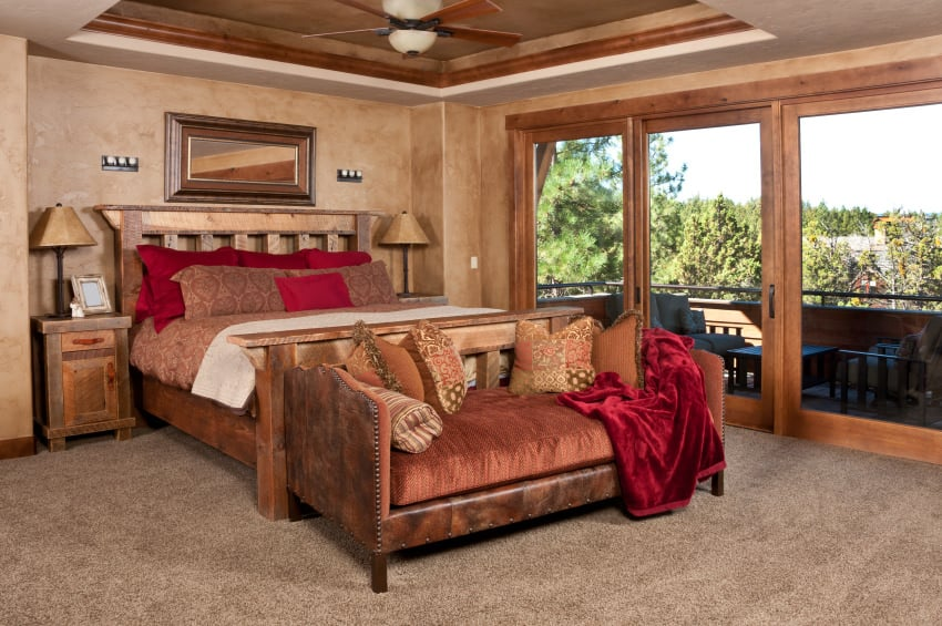 A primary bedroom with a rustic-style bed setup set under the room's tray ceiling. There's a doorway leading to the private balcony. The room has brown walls and carpet flooring.
