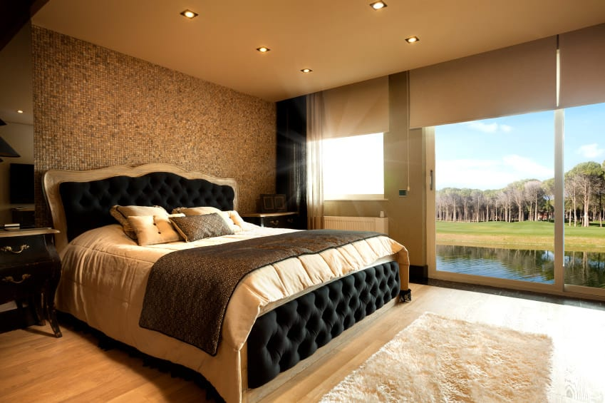 A primary bedroom boasting a stunning luxurious bed. Behind it is a very attractive wall made of tiny tiles pieces. The room also has hardwood flooring and a regular ceiling with recessed lights.