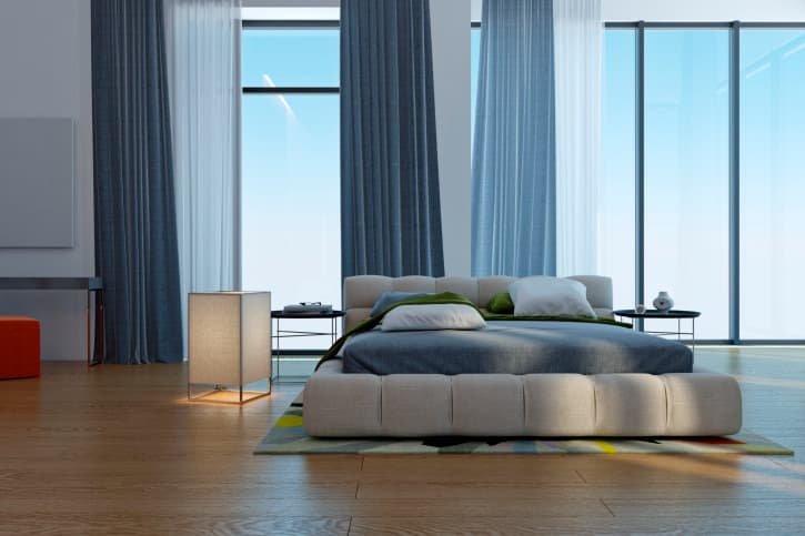 A spacious primary bedroom with hardwood flooring and tall floor-to-ceiling glass windows overlooking the breathtaking sky. The room offers a super comfy bed with two side tables.