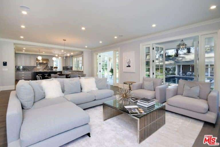 The bright living room showcases an L-shaped sofa and matching gray armchairs paired with a sleek coffee table over a beige area rug. It is illuminated by recessed ceiling lights along with natural light from the French doors.