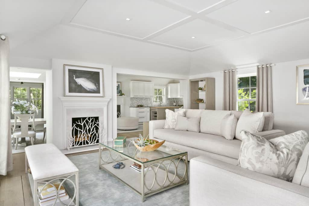 A black and white wall art hangs above the fireplace enclosed in twig screen. This room offers white seats and a stylish coffee table topped with a decorative bowl.