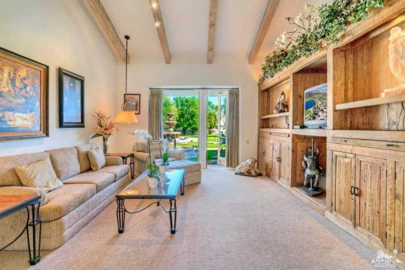 Fresh living room with built-in cabinets and a beige sectional sofa accompanied by a striped lounge chair and glass top coffee table. It has carpet flooring and a glazed door leading out to the majestic garden.