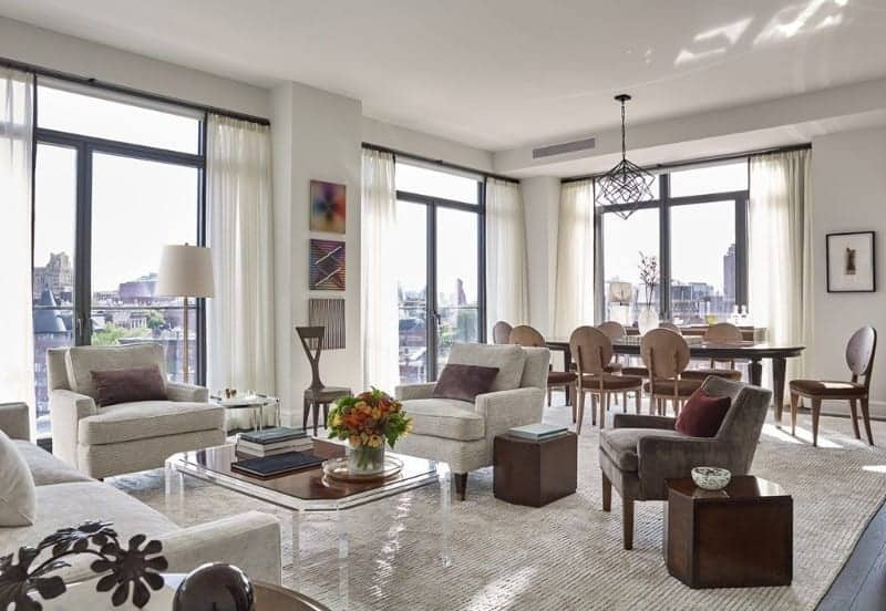 An open living room with full height glazing and dark hardwood flooring topped by a large rug. It includes cozy seats and a glass coffee table along with lovely artworks mounted on the white wall.