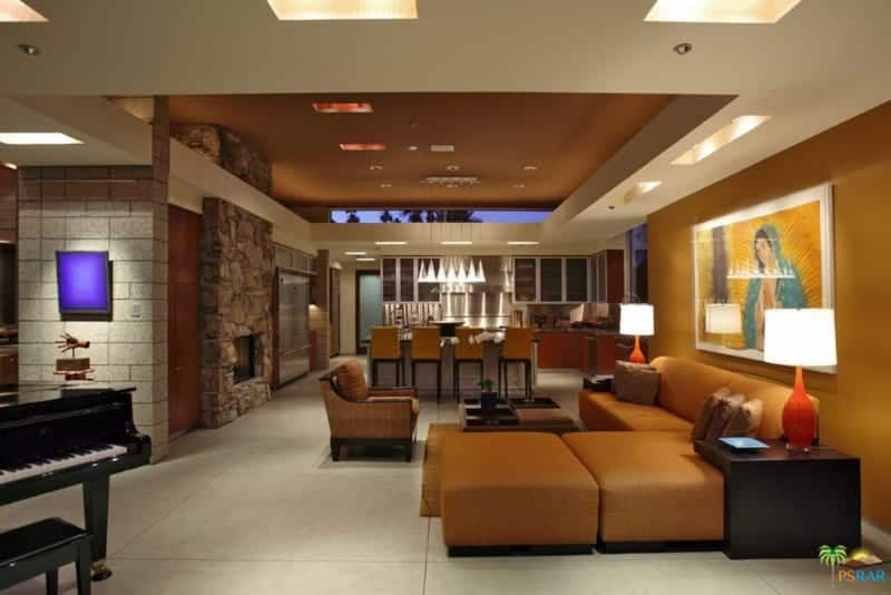 An open living area showcases a large wall art mounted on the amber wall that complements the sleek sofa flanked by black side tables. It is illuminated by orange table lamps and recessed ceiling lights.