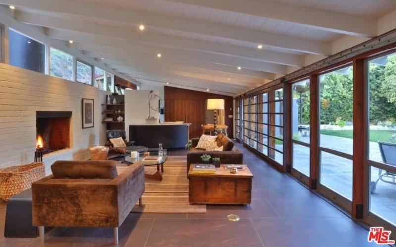 This living room offers cozy seats and a glass top coffee table facing the fireplace fitted on the white brick wall. It has shed ceiling and full height glazing allowing natural light in.