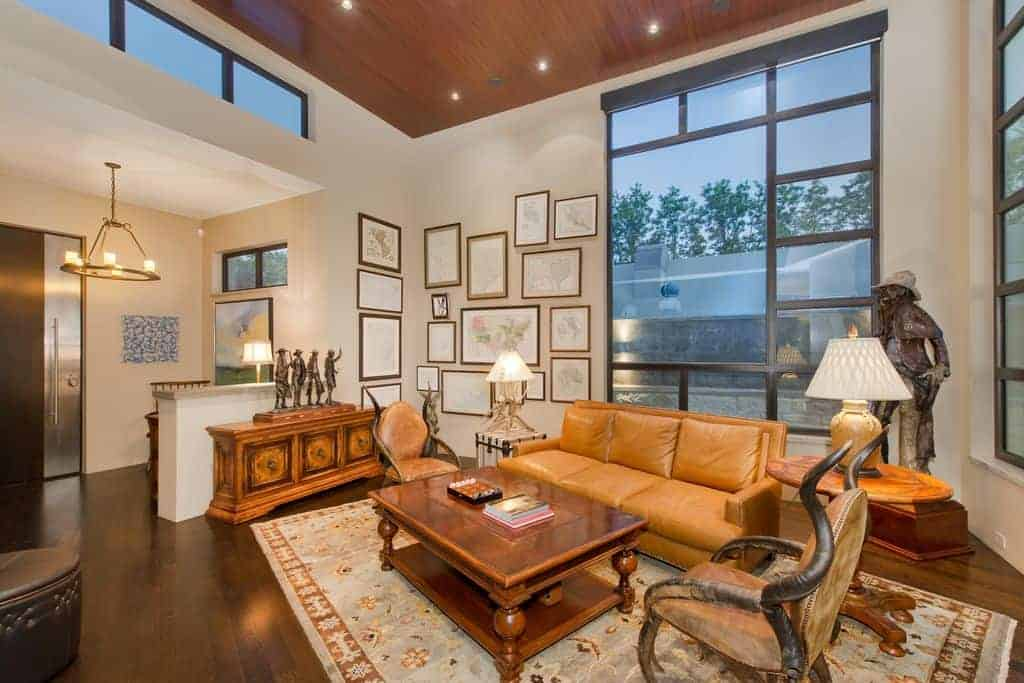 Warm living room with eccentric armchairs and a leather sectional sofa paired with a wooden coffee table over a floral area rug. It is decorated with sculptures and gallery frames mounted on the white walls.