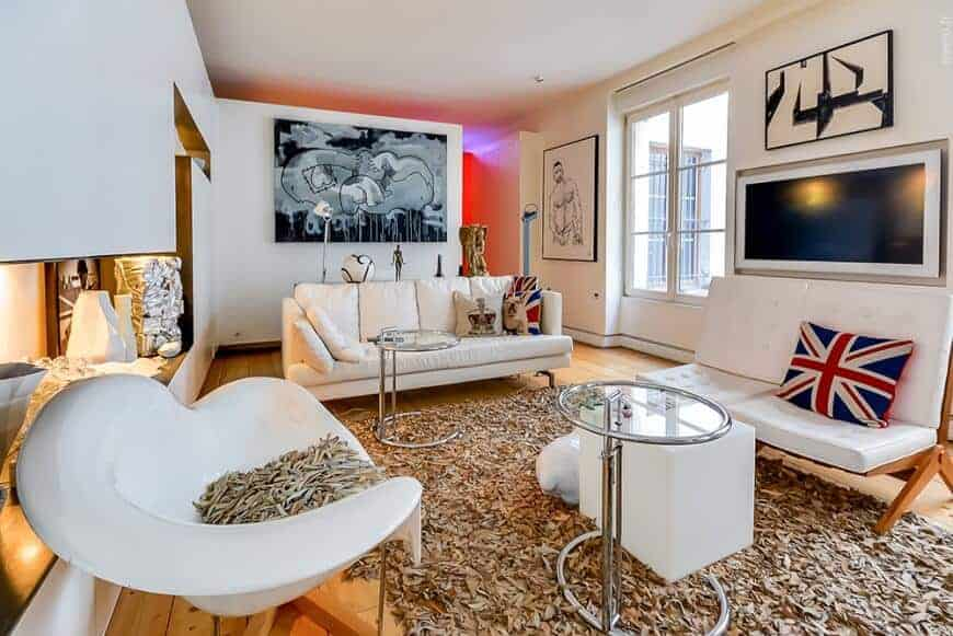 The medium-sized living room features white seats and round glass top tables on a shaggy area rug over the wide plank flooring. It is decorated with interesting artworks mounted on the white walls.