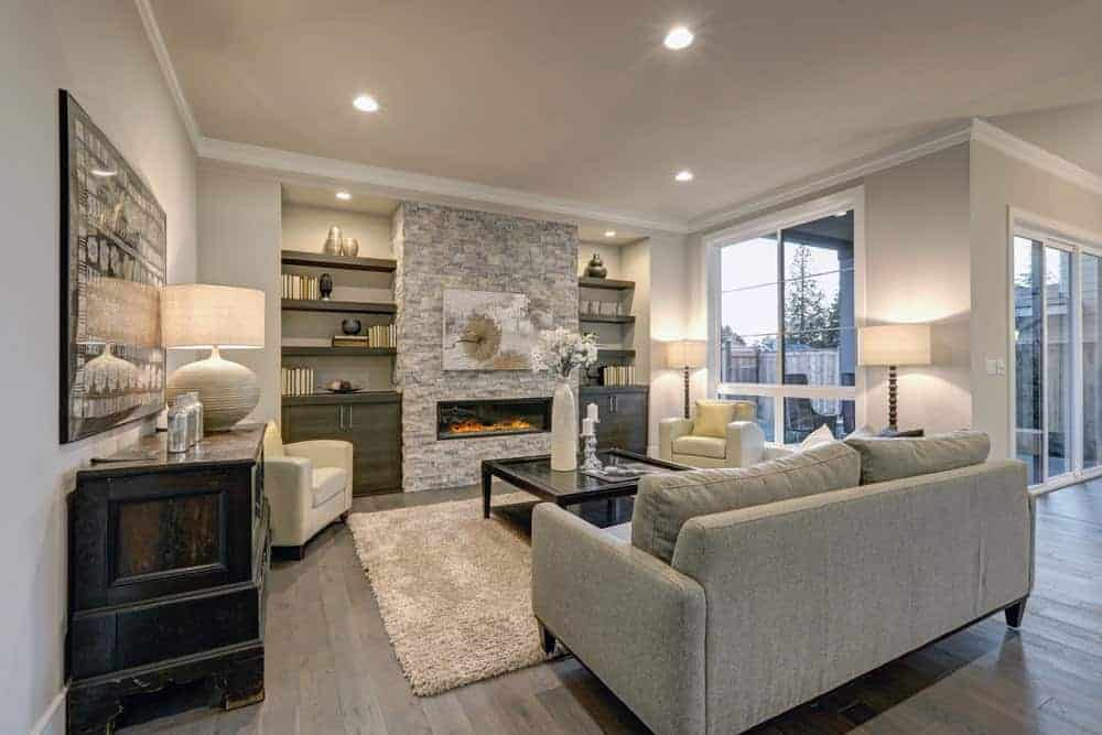 Medium-sized living room with gray walls, stone fireplace flanked by built-in shelves, and gray sofa on hardwood flooring.