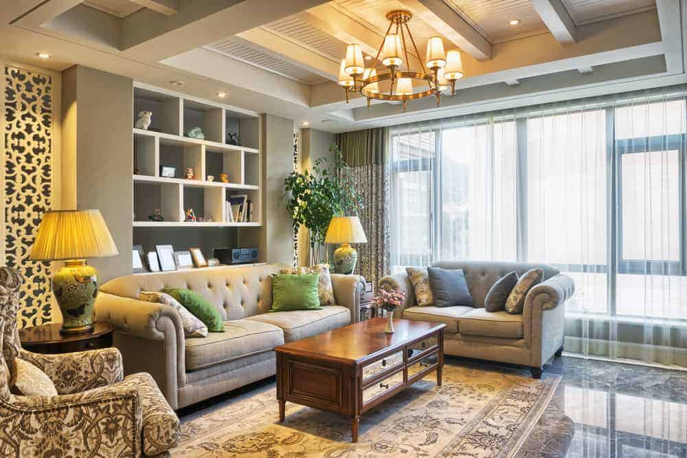 A warm chandelier that hung from the wood beam ceiling illuminates this living room offering gray tufted seats and a wooden coffee table over a classic area rug. It has marble flooring and full height windows covered in sheer curtains.