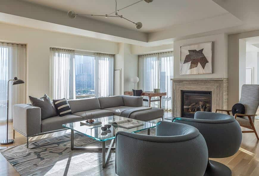 A contemporary chandelier illuminates this living room showcasing modern seats and a glass top coffee table facing the fireplace with lovely artwork on top.