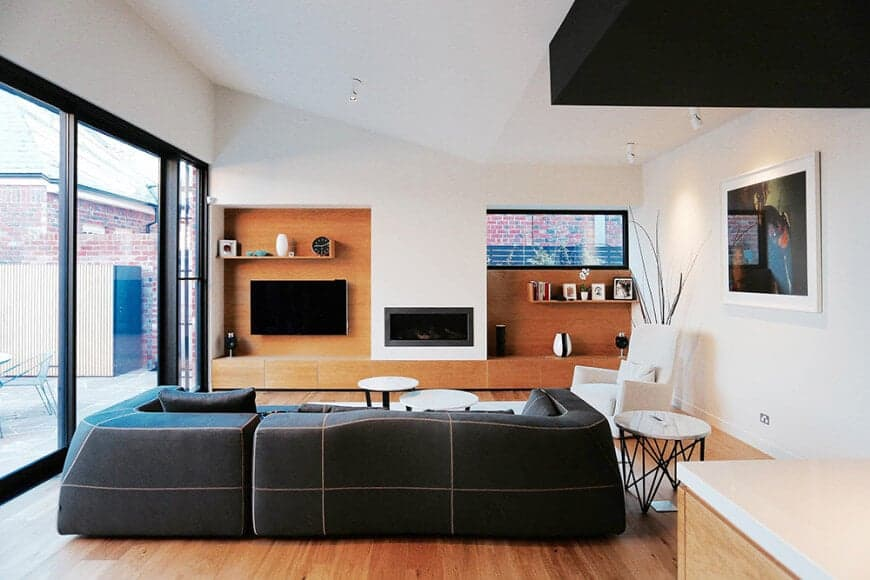 A stylish black sofa faces the fireplace flanked by a TV and floating shelves that blend in with the wood paneled wall and hardwood flooring.