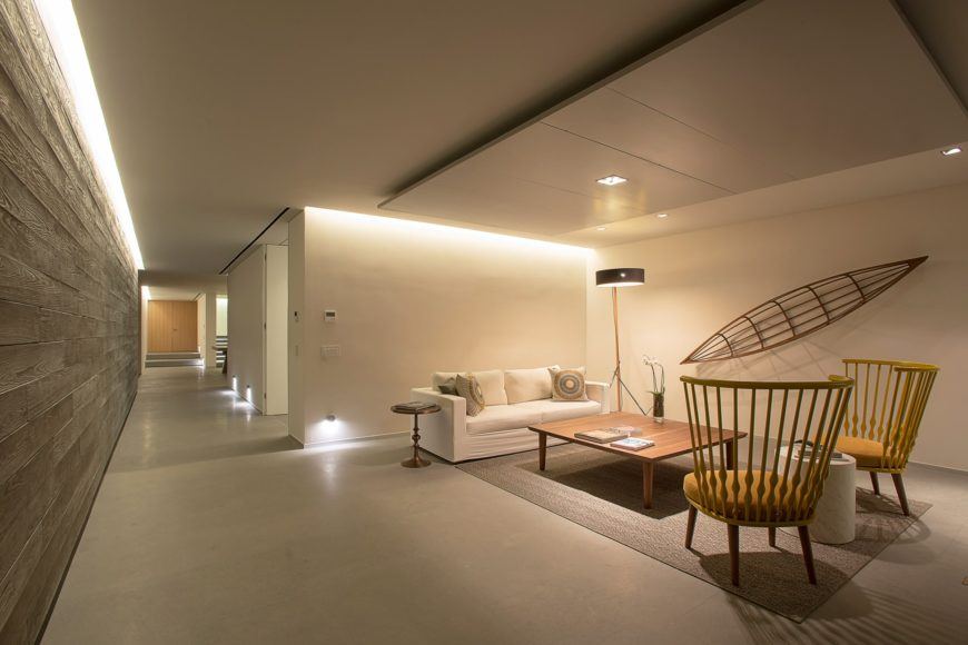 A living room along the hallway boasting a white sofa and yellow stylish chairs along with a wooden coffee table facing the wooden wall art. It is lighted by a floor lamp and recessed ceiling lights.