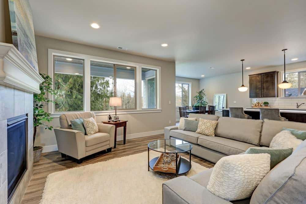 The medium-sized living room features a gray armchair and an L-shaped sofa paired with a glass top coffee table. It includes a fireplace and white shaggy rug that lays on the natural hardwood flooring.
