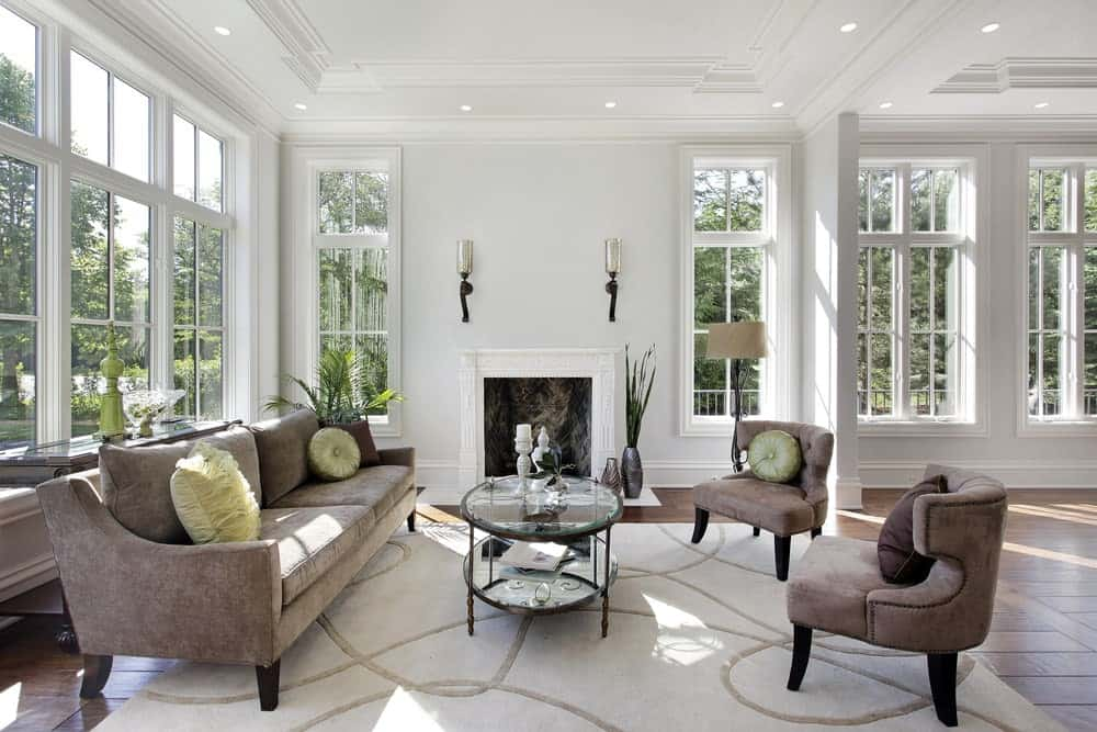 Airy living room with white framed windows and tray ceiling mounted with recessed lights. It includes brown velvet seats and a round coffee table facing the fireplace that's lighted by glass sconces.